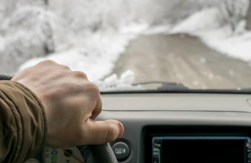 Man hand on the steering wheel of a car that moves in the snowy forest on a wet slushy road. Man`s hand on the steering wheel of a car that moves in the snowy royalty free stock image