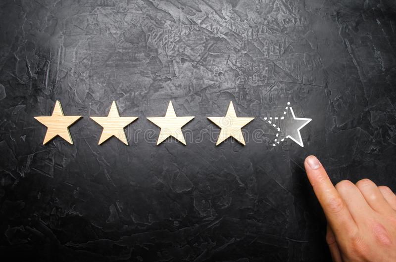 The man`s hand in the suit points to the fifth missing star. Concept acquires the fifth star rating or status. Increase prestige royalty free stock photo