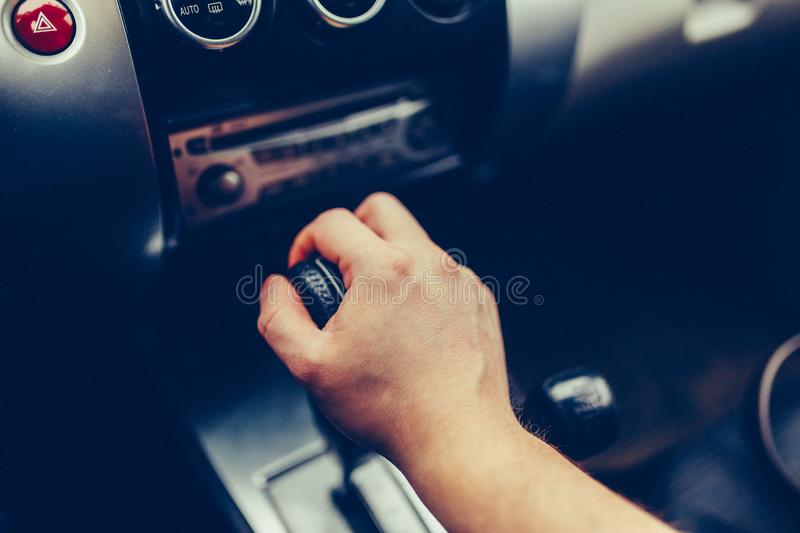 Man's hand switches automatic transmission closeup. Close up view of gear lever manual transmission car interior parts. Stylish T stock photo