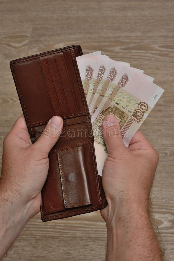 A man`s hand takes Russian banknotes from his wallet. Close Up.  royalty free stock image