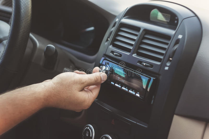 man's hand twists the volume in a retro toning car stock photography