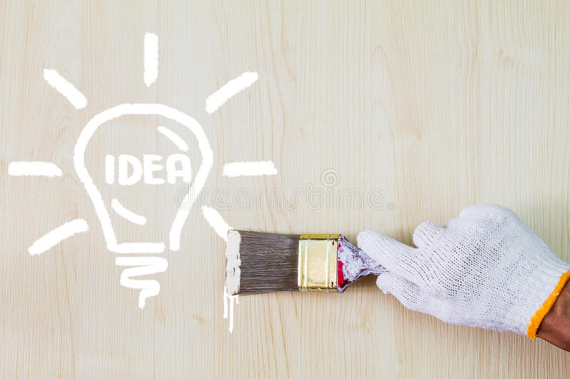 Man`s hand wearing white glove holding old grunge paintbrush and painting lightbulb on wooden wall stock photo