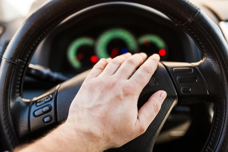 Man`s hand on the wheel of the car stock photography