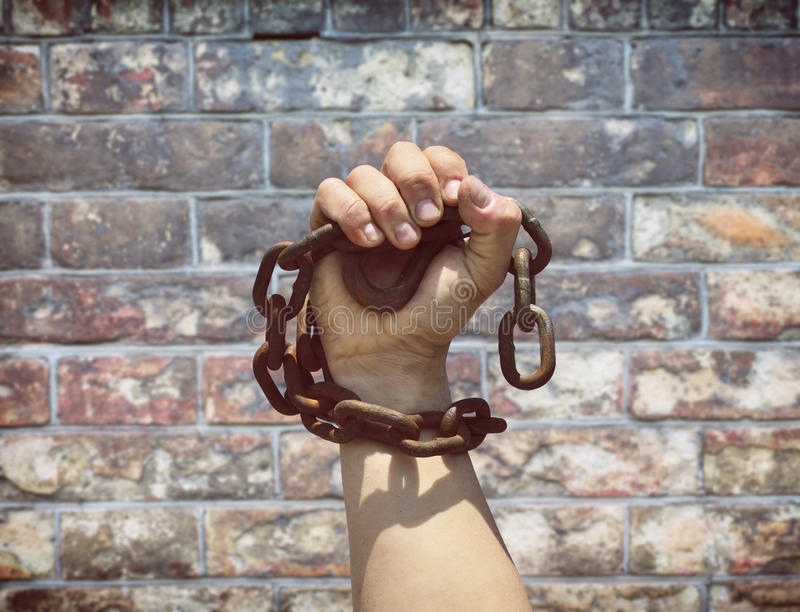 Man& x27;s hand is wrapped in a metal chain royalty free stock images