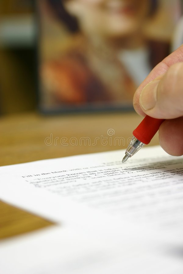 Man's hand writing at desk grading a paper stock image