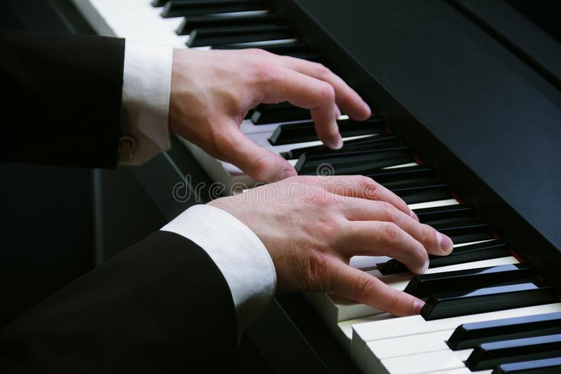 Man`s hands playing on a piano at the concert. Man`s hands in a black jacket playing on a piano at the concert royalty free stock photography