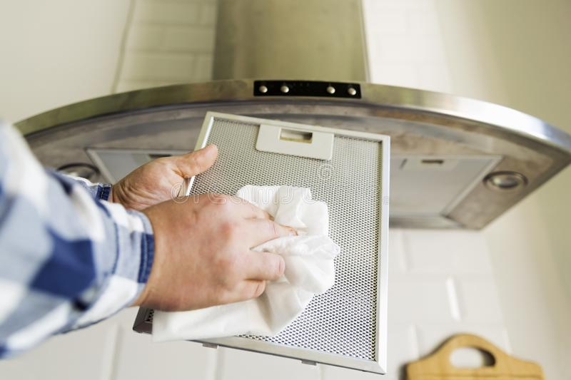 Man`s hands cleaning aluminum mesh filter for cooker hood. Housework and chores. Kitchen cooker hood on the background stock photo