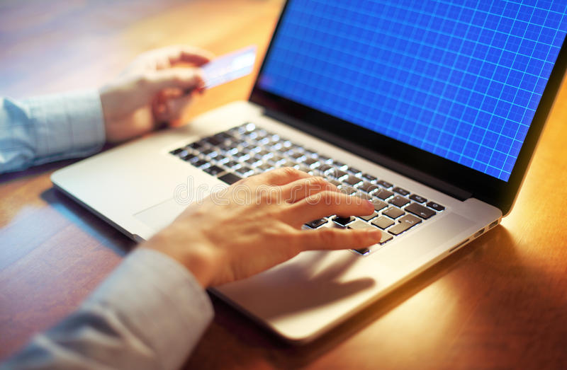 Man's hands with credit card over laptop for online sho royalty free stock images