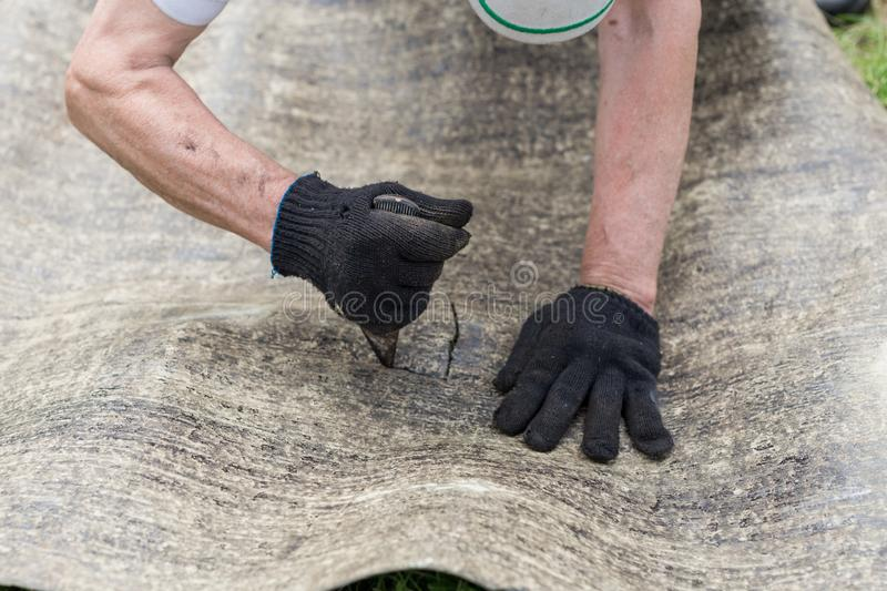 Man`s hands cutting roofing material. Ruberoid. Condtruction. Man`s hands cutting roofing material. Ruberoid. Worker royalty free stock images