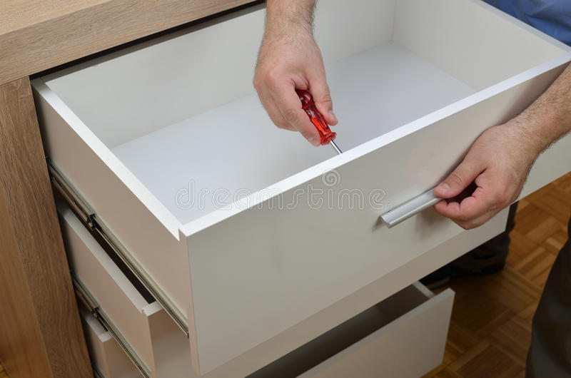 Man& x27;s Hands Fixing Drawer stock image