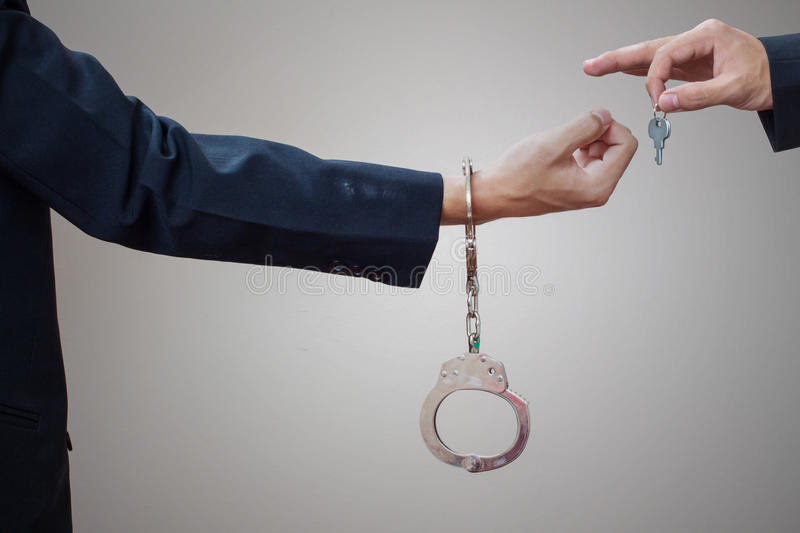 Man's hands in handcuffs and key stock image