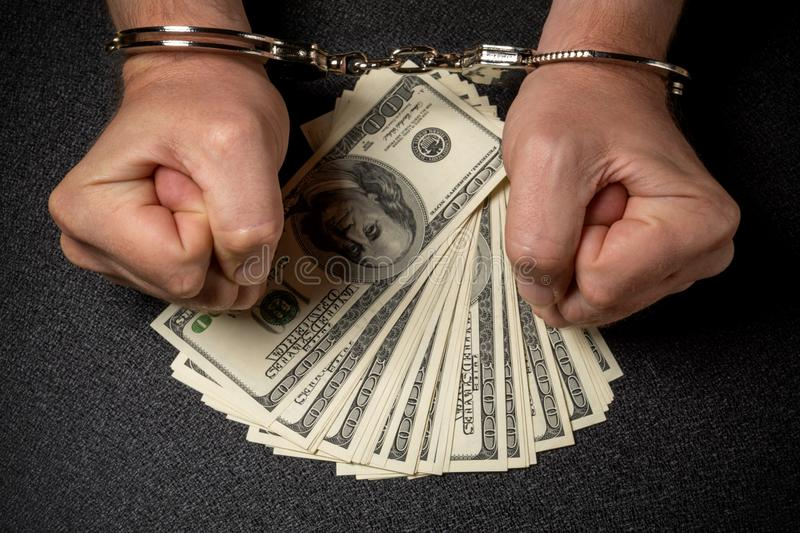 Man s hands in handcuffs and many hundred dollar american banknotes on black background. The concept of corruption. Robbery, fraud stock photography