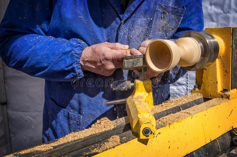 Man`s hands hold chisel near lathe royalty free stock images