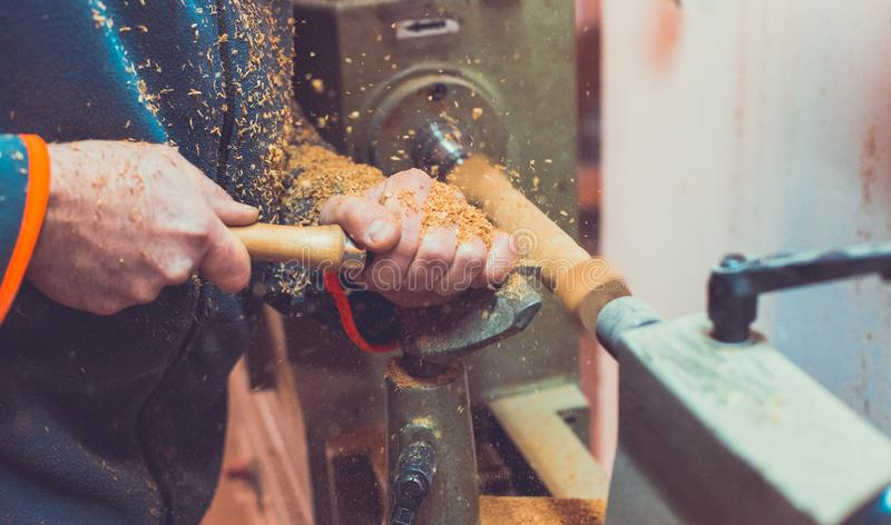 Man`s hands hold chisel near lathe, man working at small wood lathe, an artisan carves a piece of wood using a manual lathe.  stock images