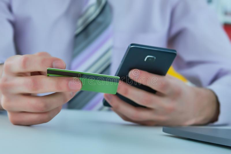 Man`s hands holding a credit card and using smart phone for online shopping. Online payment. Man`s hands holding a credit card and using smart phone for online royalty free stock photography
