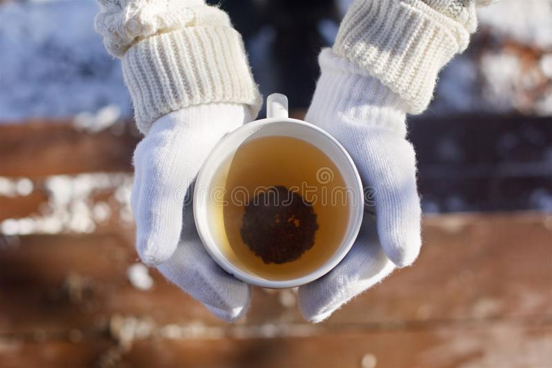 A Cup of warm tea. Man`s hands holding a Cup of warm tea. Hands in knitted gloves royalty free stock images