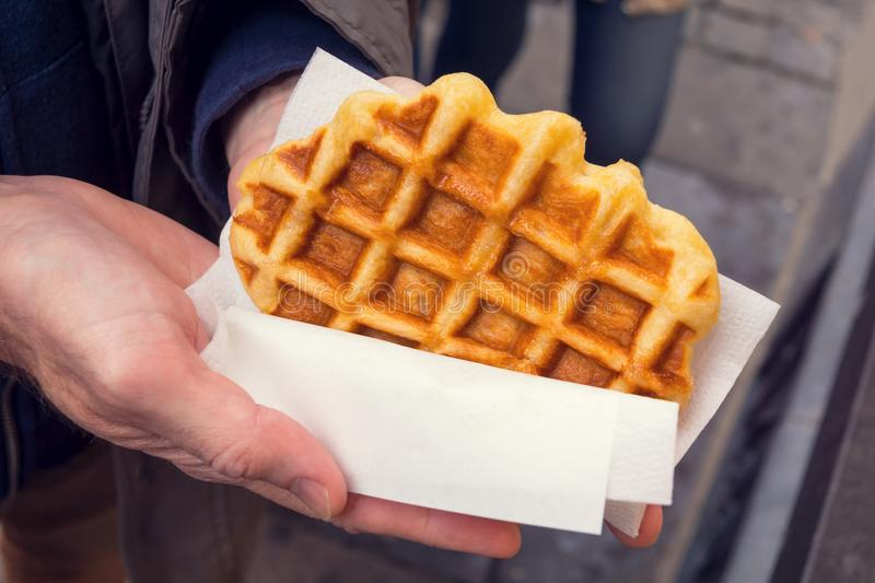 Man's Hands Holding Plain Liege Belgian Waffle royalty free stock photography