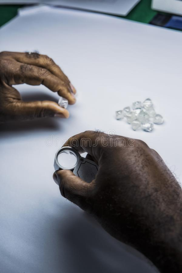 Man`s hands inspecting rough diamonds magnifying glass. stock photos