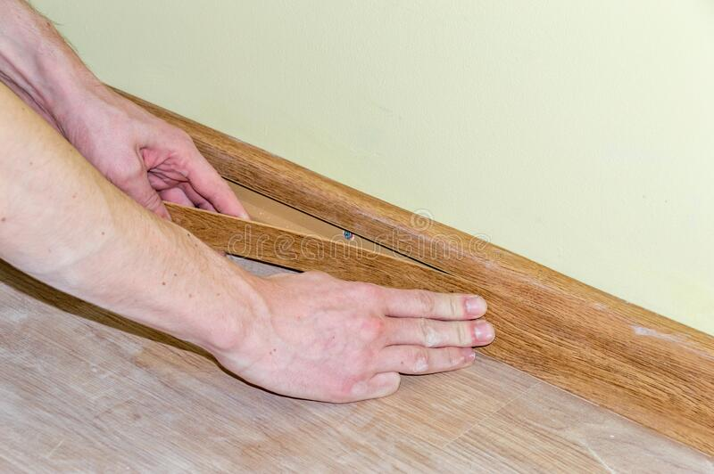 Man`s hands install decorative plastic skirting board.  stock images