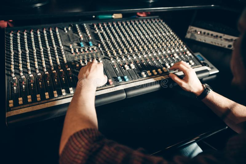 Man`s hands on the music board. Close up sound engineering . close up cropped photo stock photography