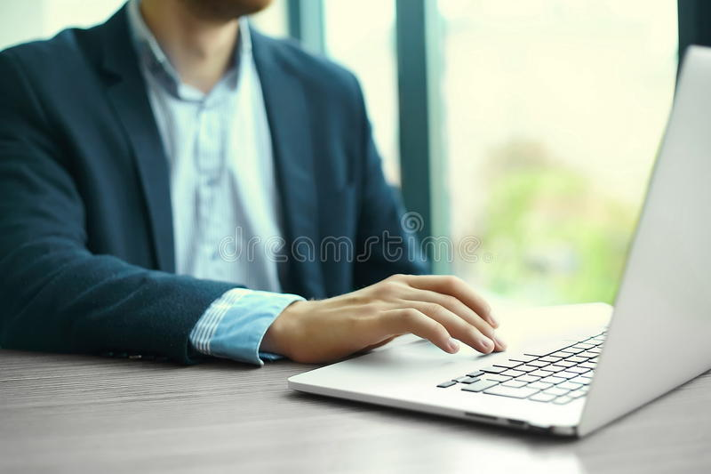 Man's hands on notebook computer, business person at workplace stock photos