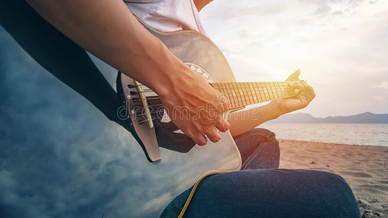 Man`s hands playing acoustic guitar, capture chords by finger on sandy beach at sunset time. playing music concept royalty free stock photography
