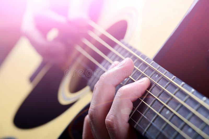 Man's hands playing acoustic guitar royalty free stock photo