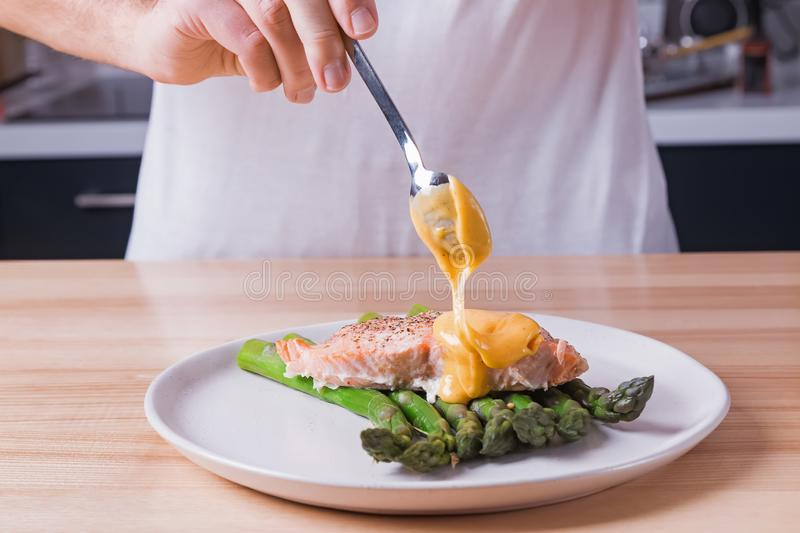 Man`s hands pouring hollandaise sauce on top of delicious baked salmon with steamed green asparagus royalty free stock image