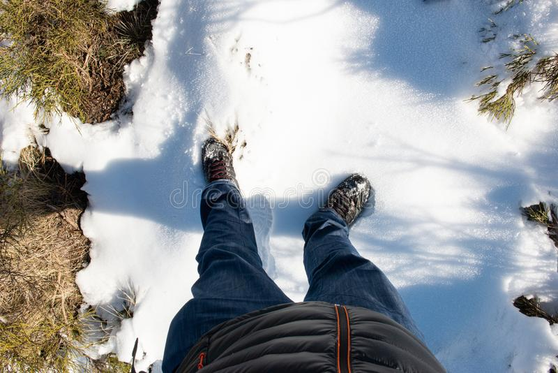 MAN'S LEG WEARING JEANS PANTS AND MOUNTAIN BOOTS FOOTING SNOW stock fotografie