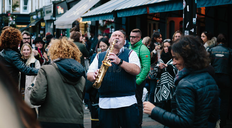 This man's music stops people who spend their time walking on the weekend market street, some of them dancing ,some of them w. Atching and laughing with stock photos