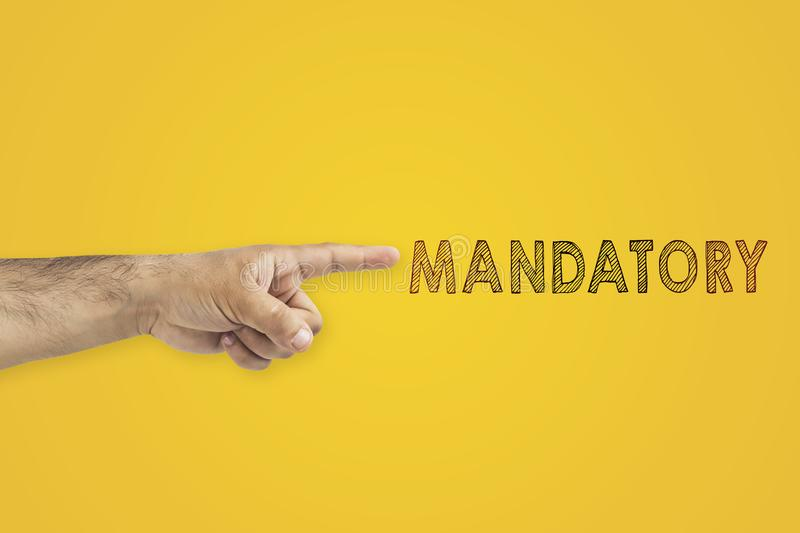 A man`s pointing hand next to the inscription mandatory on yellow background. A man`s pointing hand next to the inscription mandatory on yellow background royalty free stock photo