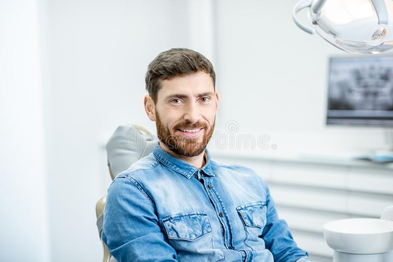 Man`s portrait in the dental office. Portrait of a handsome bearded man with healthy smile in the dental office stock image