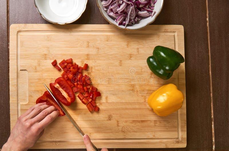 Man` s räcker bitande nya grönsaker i köket som förbereder ett mål för lunch Top besegrar beskådar royaltyfria bilder