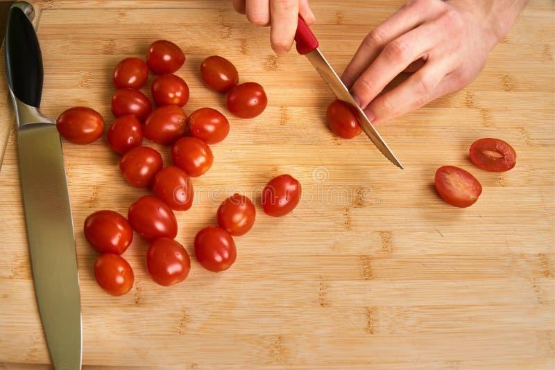 Man` s räcker bitande nya tomater i köket som förbereder ett mål för lunch Topdown sikt arkivfoto