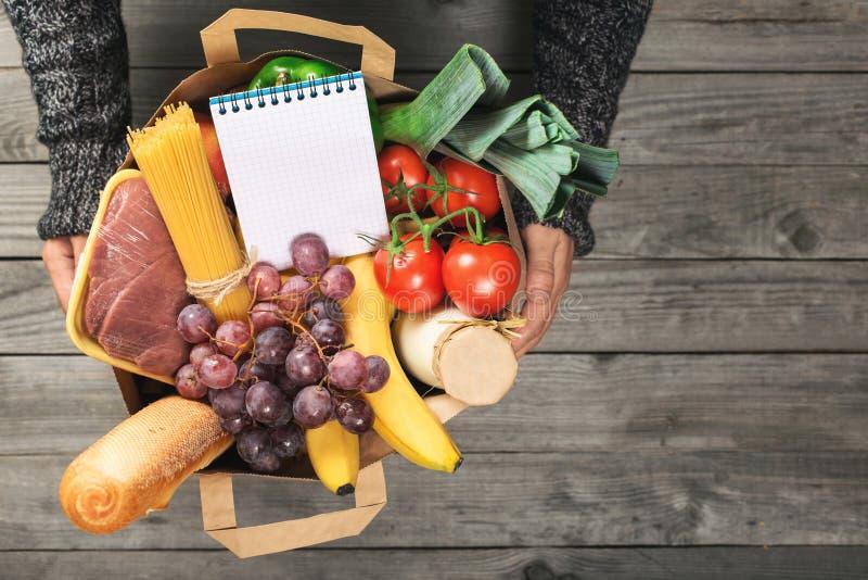 Man` s räcker den hållande pappers- påsen av livsmedel med den tomma anteckningsboken royaltyfri fotografi