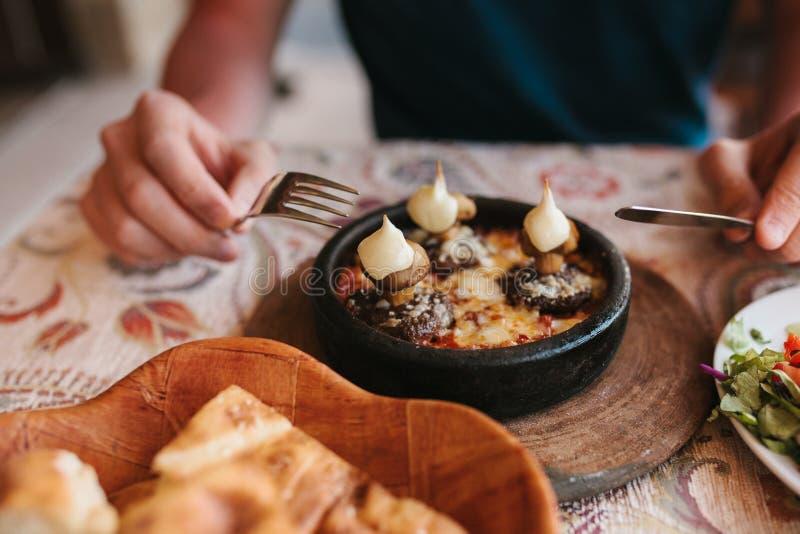 Man` s räcker hållande bestick - förbereda sig att äta maträtten med champinjoner på tabellen i kafé arkivfoto