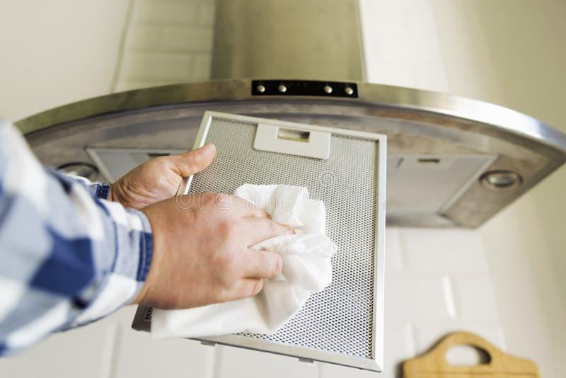Man` s räcker lokalvård det aluminum ingreppsfiltret för spishuv Hushållsarbete och sysslor Kökspishuv på bakgrunden arkivfoto