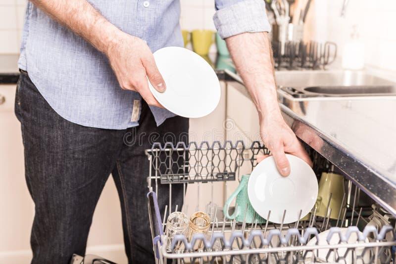 Man` s räcker päfyllningsdiskaremaskinen i det hem- köket arkivbilder