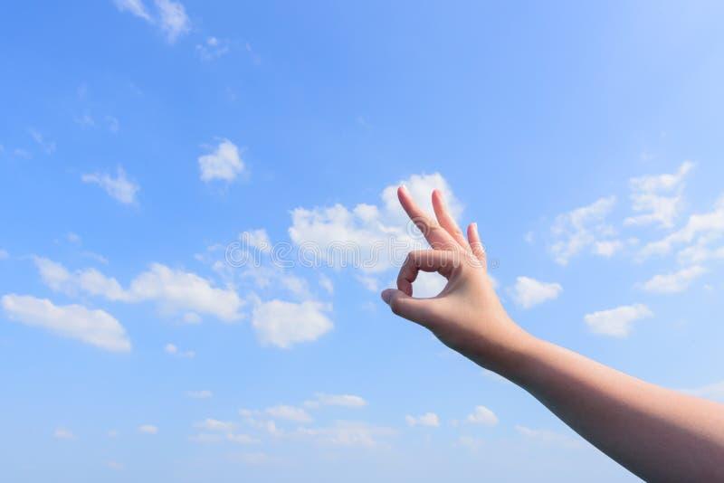 Man& x27; s ręka pokazuje Zadowalającego szyldowego niebieskiego nieba i chmur tło obraz royalty free
