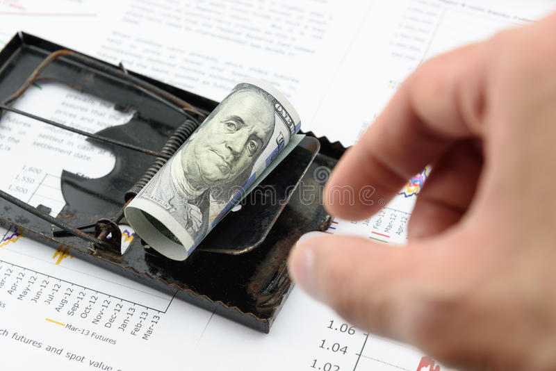 Man's right hand is preparing to pick a rolled up scroll of US 100 dollar bill on a black rat trap. royalty free stock photography