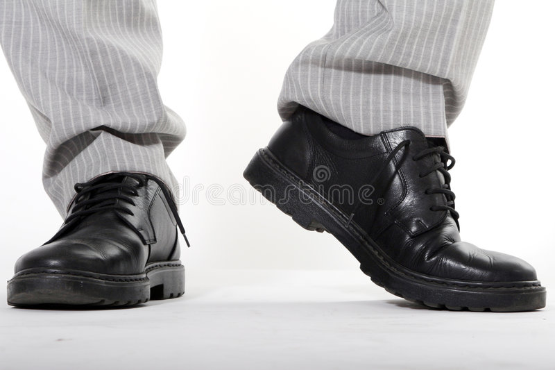 Man's Shoes. Feet of man wearing black shoes and trousers stock photo