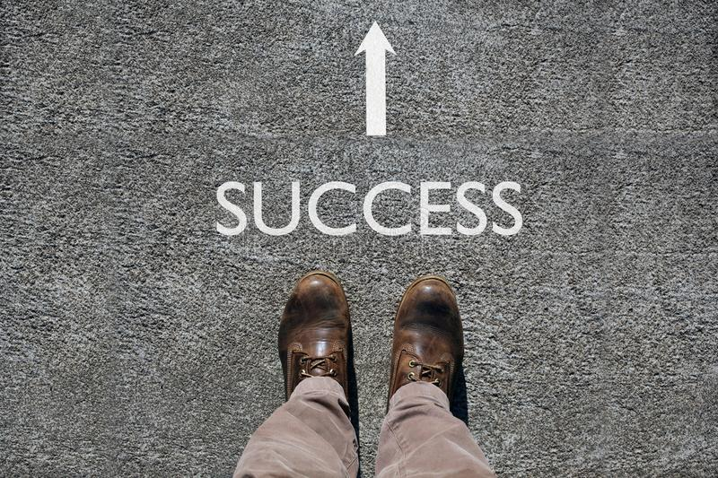 Man`s shoes view from above, word success and an arrow indicating the direction with copy spac efor your text. Man`s shoes view from above, word success and an royalty free stock photos