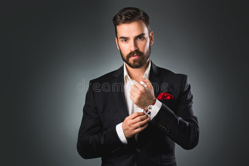 Man's style. Elegant young man getting ready. Dressing suit, shirt and cuffs. Studio shot royalty free stock images