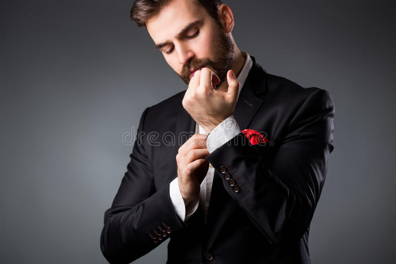 Man's style. Elegant young man getting ready. Dressing suit, shirt and cuffs. Studio shot stock images