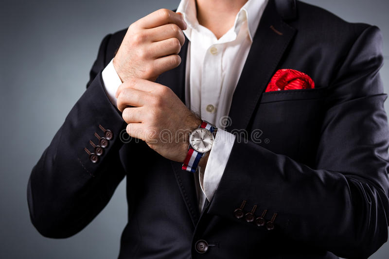 Man's style. Elegant young man getting ready. Dressing suit, shirt and cuffs. Studio shot royalty free stock photo