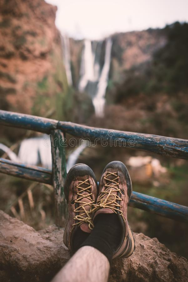 Man´s trekking shoes in a nature of Morocco - Ouzod falls. Close up of hiking boots against waterfall. Man hiking enjoying a view after trek stock photos