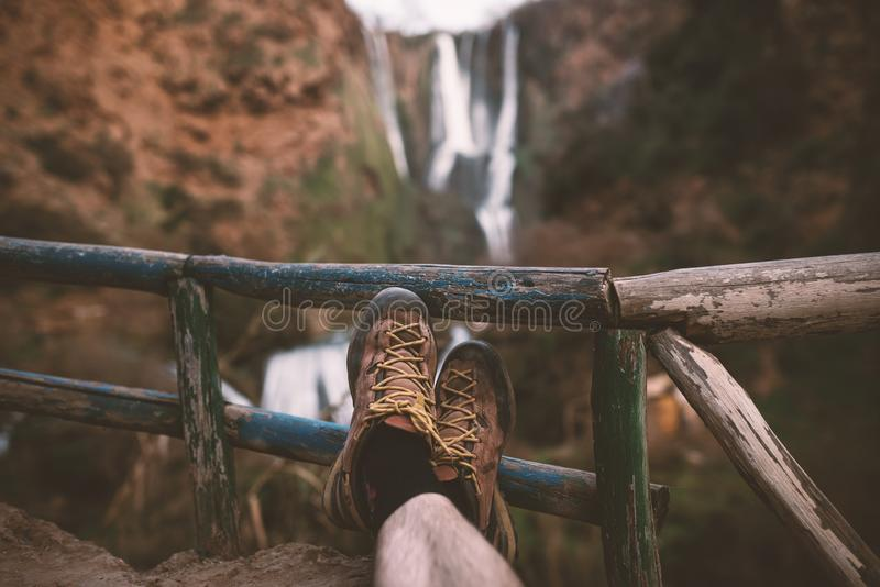 Man´s trekking shoes in a nature of Morocco - Ouzod falls. Close up of hiking boots against waterfall. Man hiking enjoying a view after trek royalty free stock photo