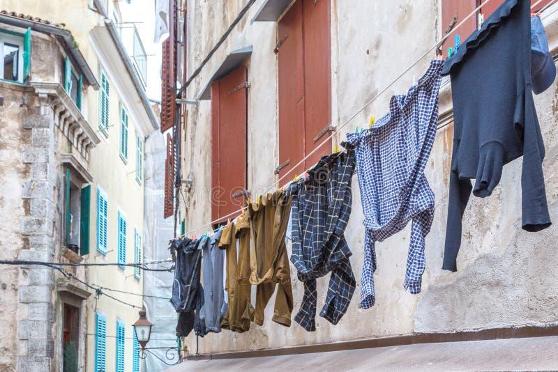Man` s tvättade tvätterit som hänger på fasaden av ett gammalt hus royaltyfri bild