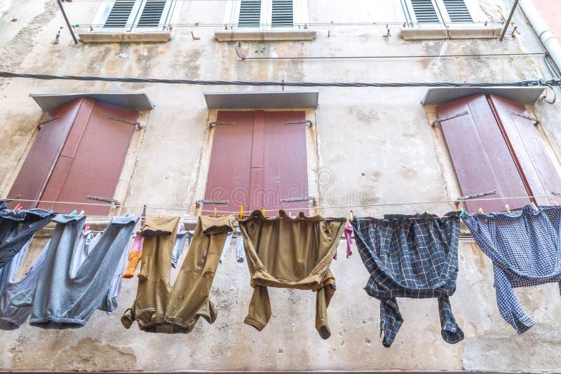 Man` s tvättade tvätterit som hänger på fasaden av ett gammalt hus royaltyfria bilder