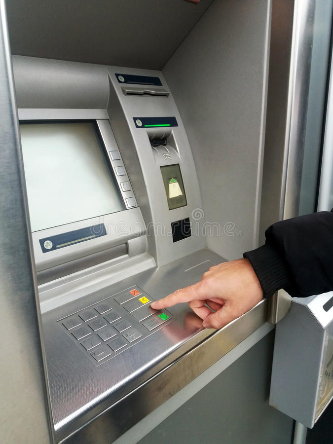 Man`s using the ATM machine with cash cards. Close-up of hand entering PIN/pass code on ATM/bank machine keypad stock image